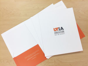 Picture of orange and white pocket folders with UTIA logo